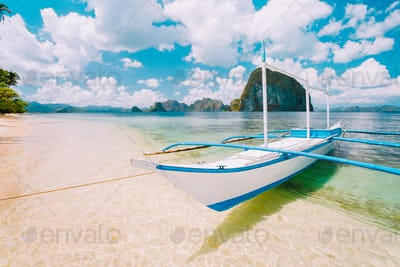 White banca island hopping boat at Las cabanas beach with amazing Pinagbuyutan island in background