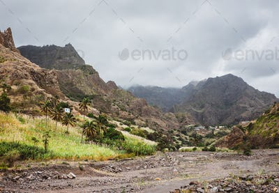 Panorama of dried-up stream surrounded by fertile green valley and rugged cliffs. Lonely white