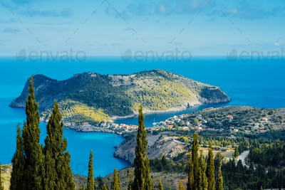 Above view to Assos village and beautiful blue sea. Cypress trees stands out in foreground