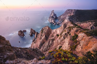 Beautiful Praia da Ursa Beach in sunset light. Surreal scenery of Sintra, Portugal. Atlantic Ocean
