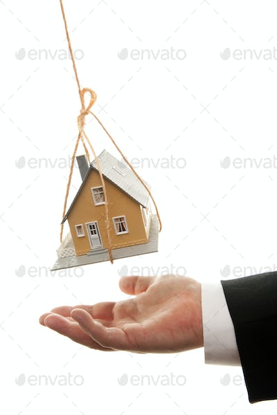 Businessman's Hand Under Dangling House