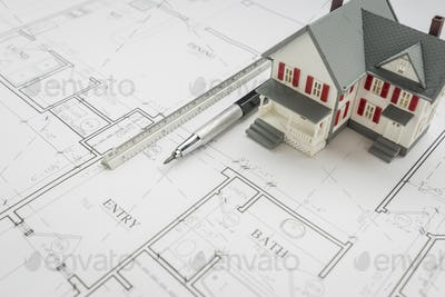 Model Home, Engineer Pencil and Ruler Resting On House Plans