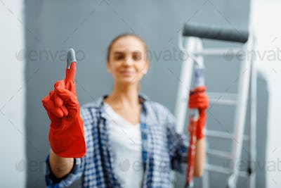 Young woman shows glove in paint, home repair