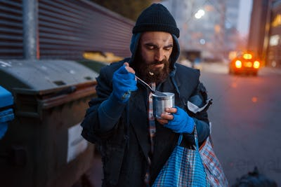 Homeless eating canned food on city street