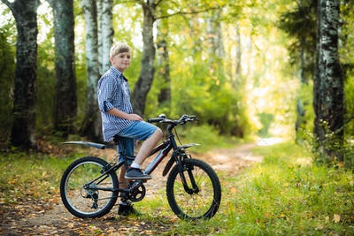 Teen boy rides a bicycle along a path in the forest. The cyclist rides fast through the springboards