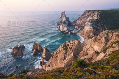 Sintra, Portugal. Praia da Ursa or Ursa Beach impressive unique sea stacks and cliffs in evening