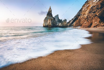 Portugal Ursa Beach. Sea stacks, white ocean wave lit by sunset light
