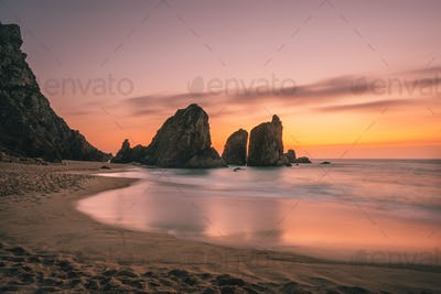 Ursa Beach near Cape Roca at Atlantic Ocean coast in Portugal. Sand beach with sea stacks in evening