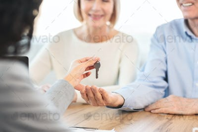 Happy mature couple getting key of their new place