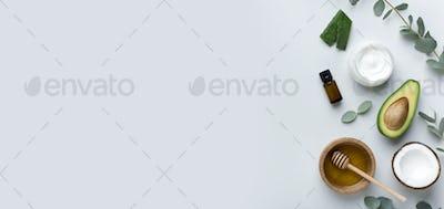 Body cream and avocado half, essential oils and bowl of honey
