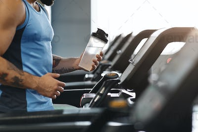 Sportsman drinking water during cardio workout on treadmill