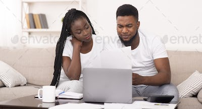Black couple managing family budget at home together, reading financial documents