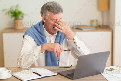 Elderly Businessman At Laptop Massaging Nosebridge Having Headache In Office