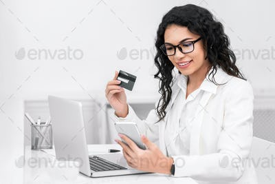 Latin businesswoman booking tickets online using phone