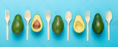 Eco disposable tableware with avocado seeds on blue