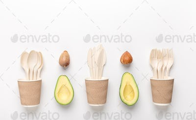 Eco plastic disposable tableware in wooden cup with avocado seeds
