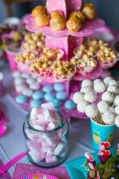 Marshmallow, sweet colored meringues, popcorn, custard cakes and white cake pops on desert table