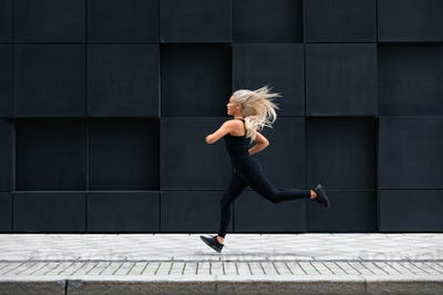 Fit young woman running in minimalist urban city environment