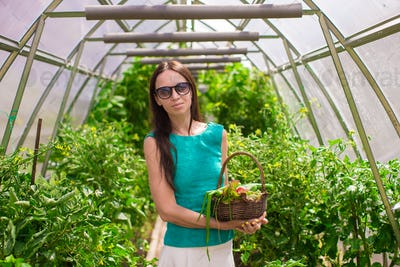 young woman holding a basket of greenery and onion in the greenhouse