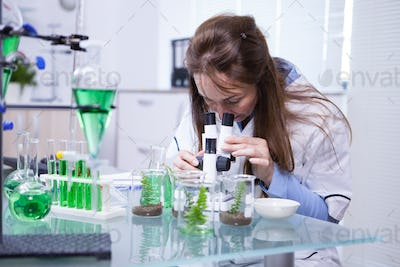 Female scientist adjusting her microscope in a biotechnology lab