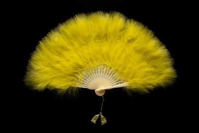 Yellow Chinese folding fan on a black background