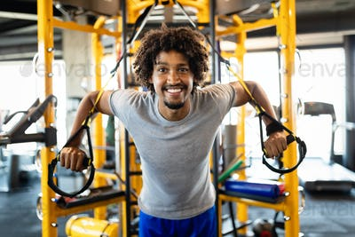 Handsome fit man having fitness TRX training at gym