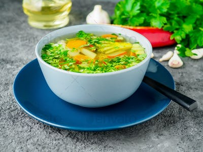 Healthy spring vegetable dietary vegetarian soup, gray concrete background, side view, close up.