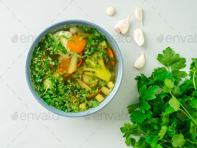 Healthy spring vegetable dietary vegetarian soup, gray concrete background, top view, close up.