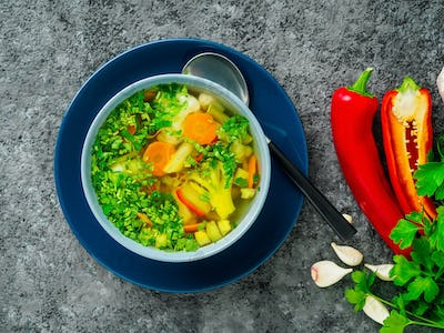 Healthy spring vegetable dietary vegetarian soup, gray dark concrete background, top view, close up.