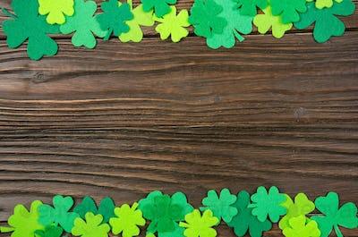 Happy Saint Patrick's mockup of handmade felt shamrock clover leaves on wooden background.