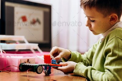 Boy dressed in green sweater sits at the table with computer and robotic constructor and makes a