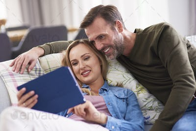 Mature couple using a tablet in living room