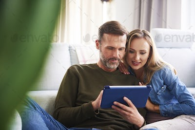 Couple using a tablet in living room