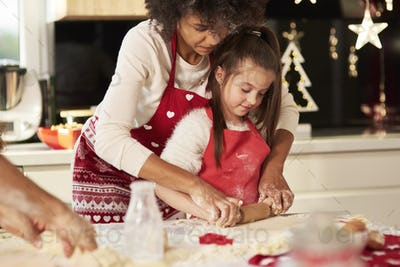 Girl making cookies with mom