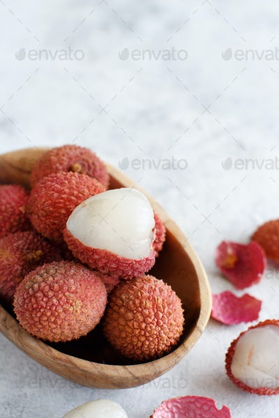 Fresh litchi fruits in a bowl in a white table