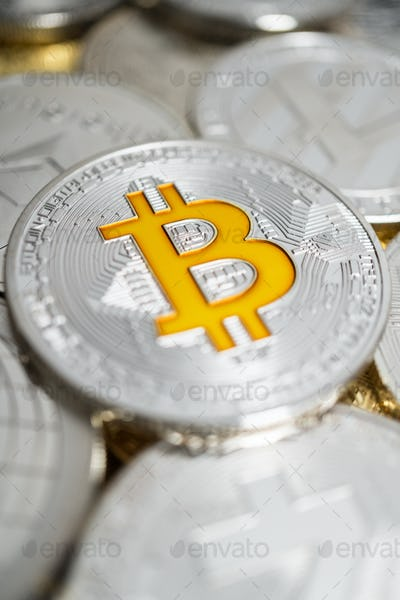 Close-Up Of Bitcoin Physical Coin On Stack Of Many Other Cryptocurrencies