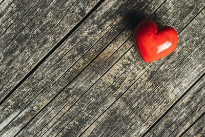 Red heart on old wooden table.
