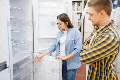 Couple choosing refrigerator in electronics store