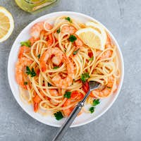 Seafood Pasta spaghetti with shrimps and parsley on gray stone background.
