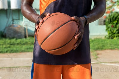Young African American man holding a basket ball in an outdoors court, Cuba