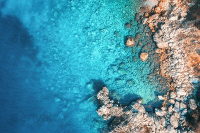 Aerial view of rocky beach and sea with transparent blue water