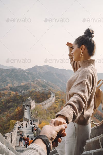 beautiful girl holding her husband's hand at the Great Wall of China