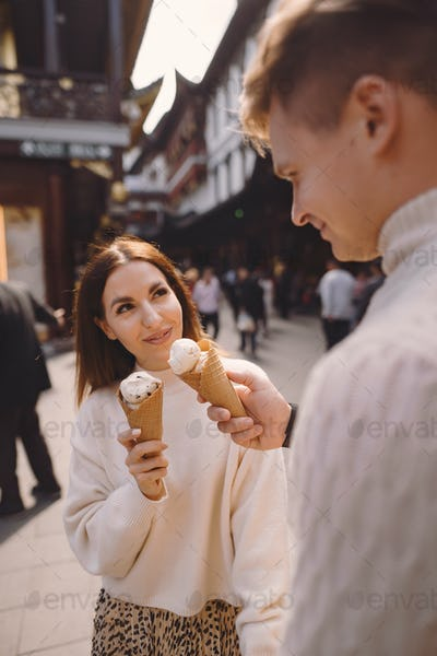 newlywed couple eating ice cream from a cone on a street in Shanghai near Yuyuan China