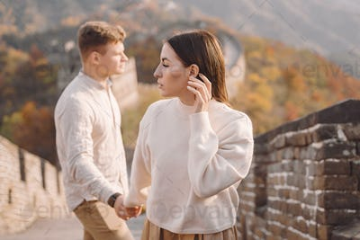 beautiful young couple holding hands and showing affection at the Great Wall of China