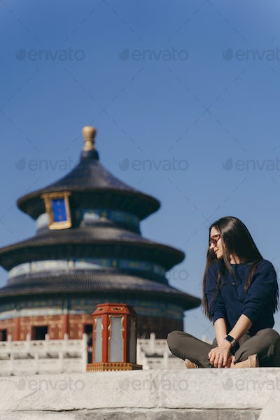 brunette girl sitting on the steps by temple of heven in China
