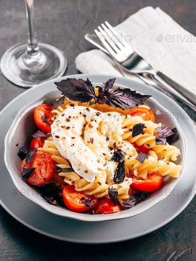 Pasta fusilli with cherry, mozarella and basil