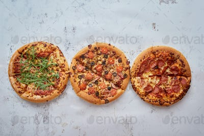 Three different kind of pizzas placed in a row on white rusty table