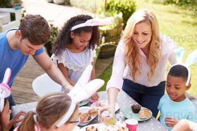 Parents With Children Wearing Bunny Ears Enjoying Outdoor Easter Party In Garden At Home