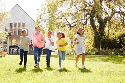Group Of Children Running Across Garden Lawn At Home Looking Into Camera