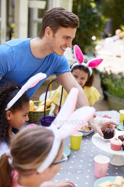 Father With Children Wearing Bunny Ears Enjoying Outdoor Easter Party In Garden At Home